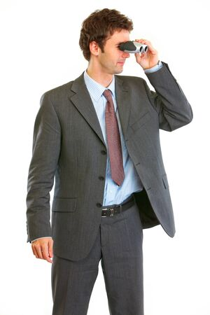 Modern businessman looking through binoculars in corner  photo