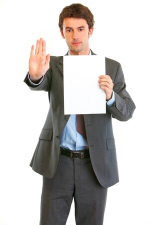 Serious modern businessman holding blank paper and showing stop gesture  photo