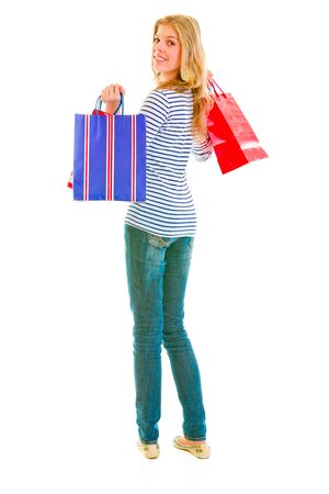 Smiling teen girl with shopping bags looking back  photo