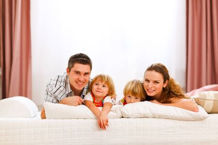 Family portrait of mother father and twins daughters on bed photo