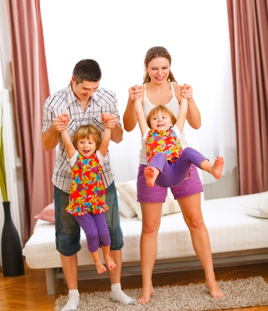playing on divan: Mother and father having fun with twins daughters Stock Photo