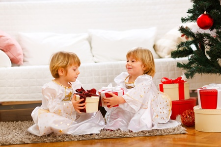 Two lovely twins girl exchanging presents near under Christmas tree photo