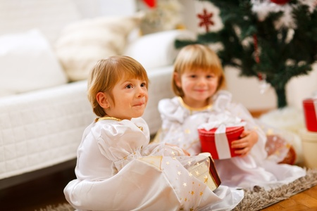 Two twins girls sitting with presents near Christmas tree photo