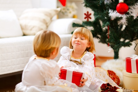 Happy girl sitting near Christmas tree and presenting gift to her sister photo