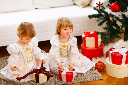 Two cute twins girls opening presents near Christmas tree photo