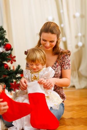 Mom looking with daughter inside of Christmas socks near Christmas tree photo