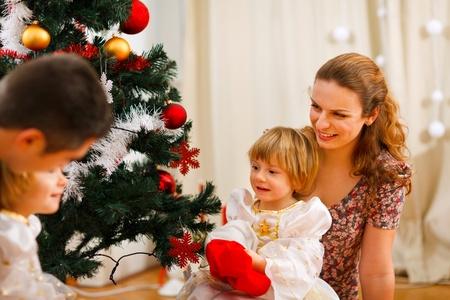 Family spending time near Christmas tree photo