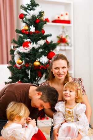 Parents with two daughters spending time near Christmas tree photo