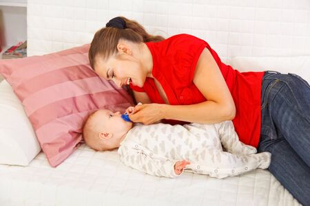 Happy mother laying on couch and giving soother to baby Stock Photo - 12115058