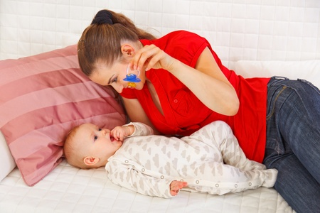 playing on divan: Young mother laying on sofa and playing with baby