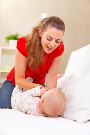 divan: Madre joven que juega con el beb� en el div�n