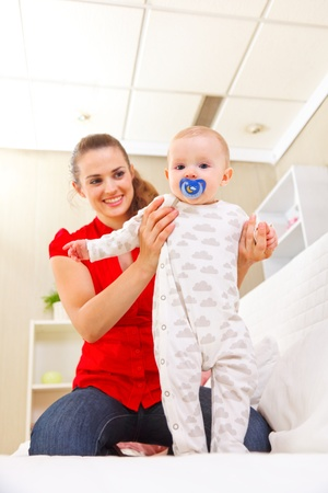 Smiling mother helping baby learn to walk Stock Photo - 12115045