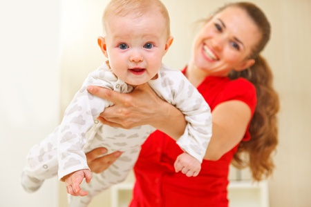 Happy mother and lovely baby playing on divan Stock Photo - 12114343