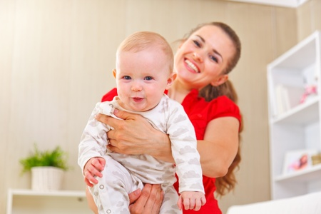 Smiling mother and adorable baby playing at home Stock Photo - 12115041