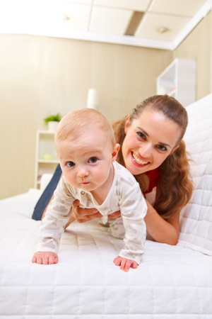 interested baby: Happy mother and interested baby playing on divan Stock Photo