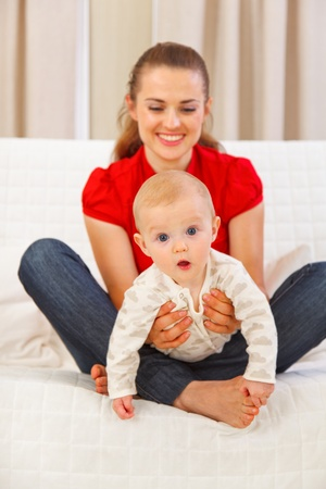 playing on divan: Interested baby playing on mothers laps