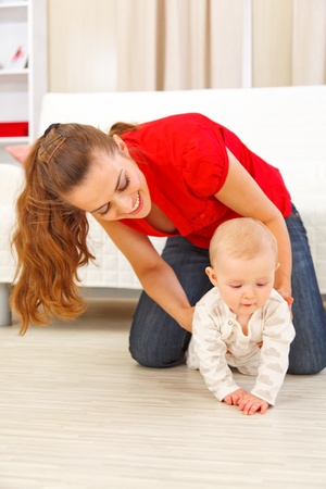 to creep: Mother helping cheerful baby learn to creep