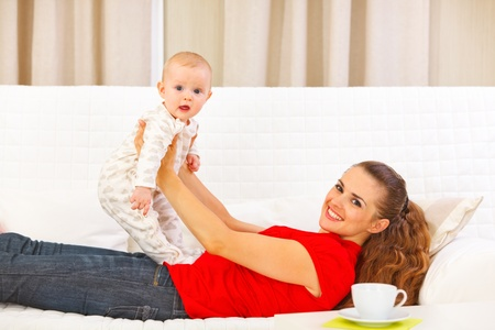 Smiling mother and adorable baby playing on couch Stock Photo - 12115056