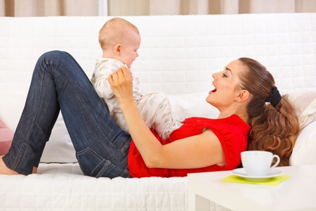 playing on divan: Smiling mother and cute baby playing on divan