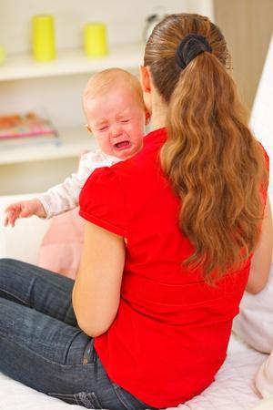 bambino che piange: Madre calmante bambino che piange Archivio Fotografico