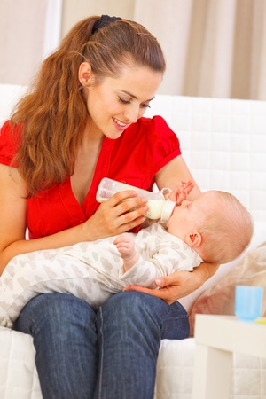 Happy mother sitting on sofa and feeding baby Stock Photo - 12115064