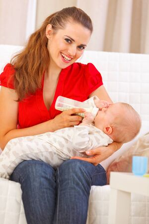 Smiling young mother sitting on couch and feeding baby Stock Photo - 12115060