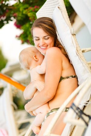 Happy young mother laying on sunbed and hugging baby photo