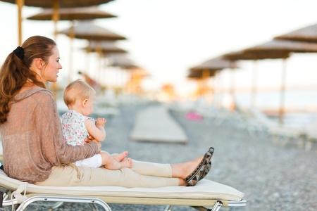 Young mother sitting with baby on sunbed on the beach at evening and looking into the distance photo