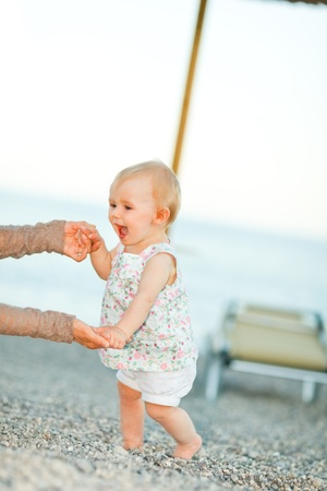the first step: Happy baby on the beach trying to start walking with mothers help