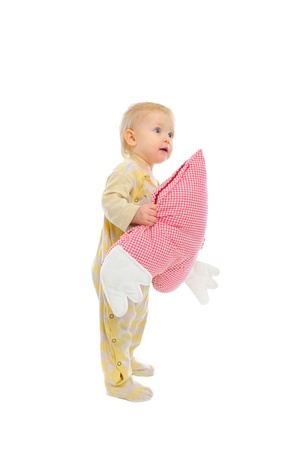 interested baby: Interested baby standing with heart shaped pillow and looking in corner Stock Photo