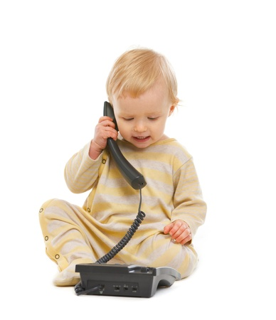 daycare: Adorable baby speaking on phone isolated on white