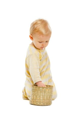 interested baby: Interested baby checking inside of basket isolated on white Stock Photo