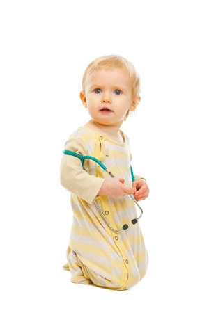 aghast: Confused baby with stethoscope sitting on floor isolated on white Stock Photo