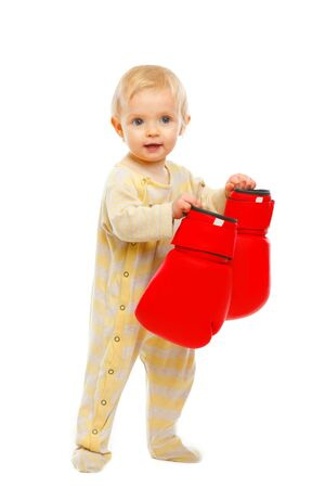 Adorable baby standing with boxing gloves isolated on white Stock Photo - 12349391