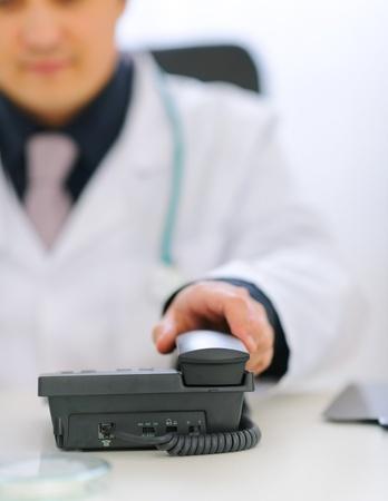 phone handset: Primo piano a portata di mano i medici prendere cornetta del telefono