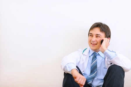 Medical doctor sitting on floor and talking mobile Stock Photo - 12350283