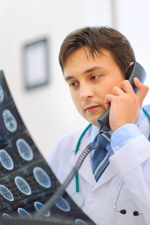 Medical doctor holding patients tomography and speaking phone Stock Photo - 12349931