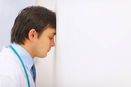 weariness: M�dico cansado apoy� la cabeza contra una pared