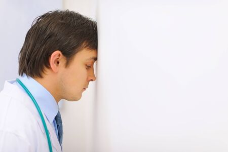 weariness: Tired medical doctor leaned his head into a wall Stock Photo