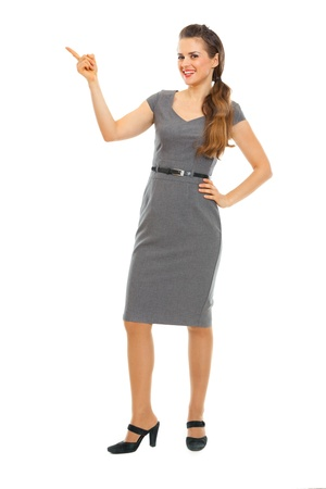 Full length portrait of business woman pointing in corner Stock Photo