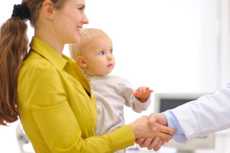 thanking: Closeup on mother with baby thanking pediatrician doctor for examination