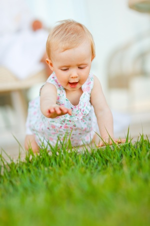 Happy baby trying to touch grass Stock Photo - 12351588
