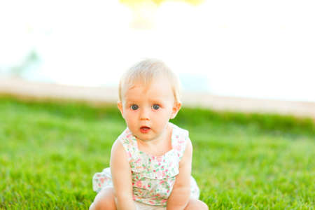 interested baby: Portrait of interested baby sitting on grass