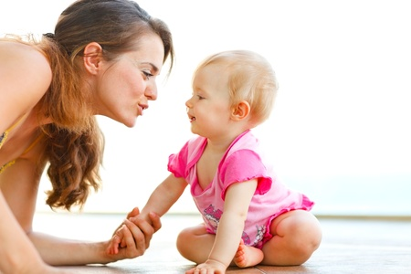 Young mother playing with baby on floor Stock Photo - 12351461