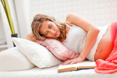 pregnant relaxing on sofa: Pregnant woman fell asleep while reading book Stock Photo