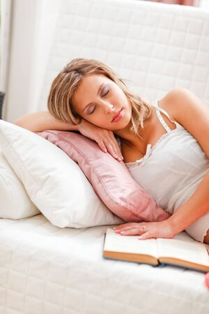 Young woman fell asleep while reading book photo