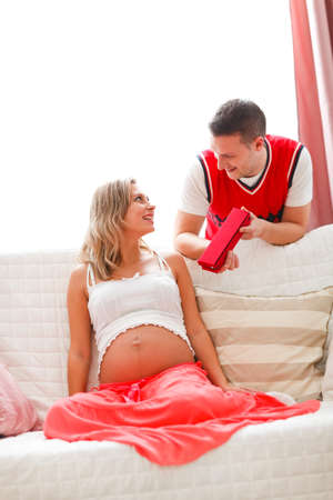 Young husband making present to pregnant wife photo