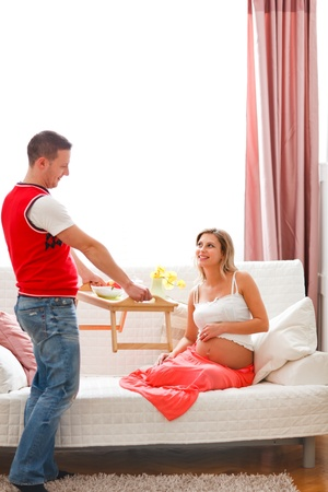 Young guy bring breakfast to happy pregnant wife photo