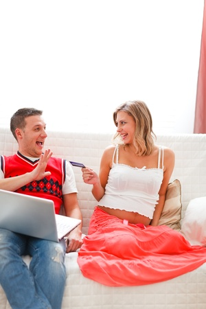Happy pregnant woman with husband shopping on Internet photo