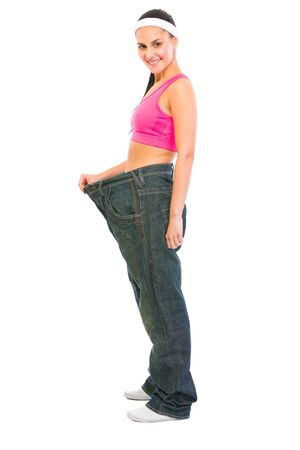 oversize: Slim girl pulling oversize jeans. Weight loss concept Stock Photo
